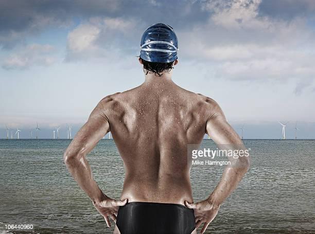 athletic male swimmer standing by the sea - calzoncini da bagno foto e immagini stock