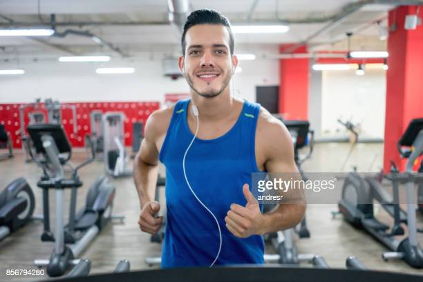 Athletic man at the gym running on the treadmill