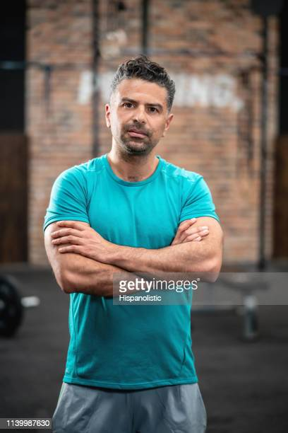 athletic man at the gym with arms crossed facing camera very serious - hispanolistic stock photos and pictures