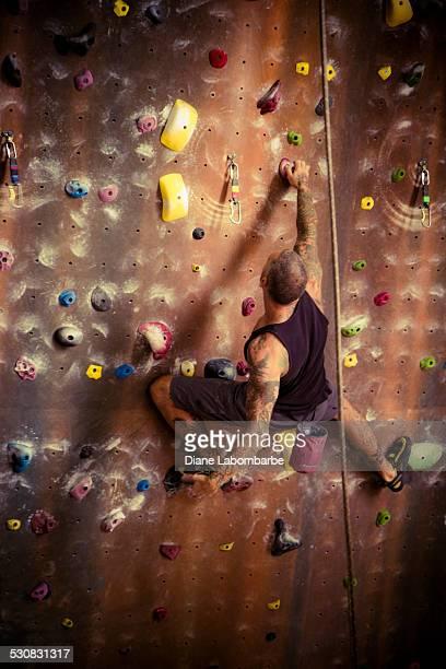 Sportlichen Mann Klettern im Fels-Kletterwand-Center