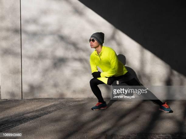 athletic man crouching down, stretching his leg before running. - homens de idade mediana - fotografias e filmes do acervo