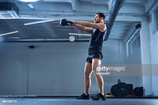 athletic man doing kettlebell swing exercise at gym - kettlebell - fotografias e filmes do acervo