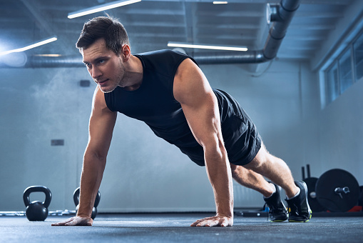 Athletic man doing pushups exercise at gym - gettyimageskorea