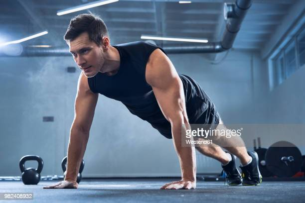 athletic man doing pushups exercise at gym - bodybuilding stockfoto's en -beelden