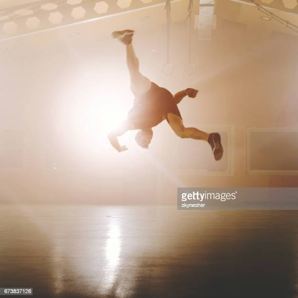 athletic man doing somersault while exercising in health club. - somersault stock pictures, royalty-free photos & images