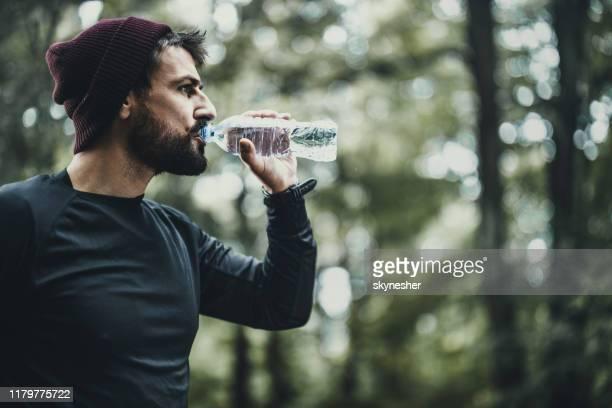 athletischer mann, der frisches wasser auf einer pause in der natur trinkt. - durst stock-fotos und bilder