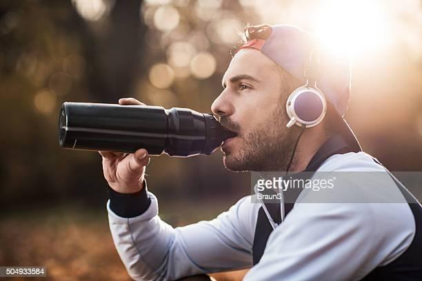アスレチック男性飲料水自然の音楽を聴きながら、ます。
