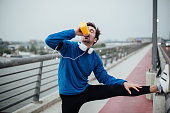 young man exercising outdoors drinking water