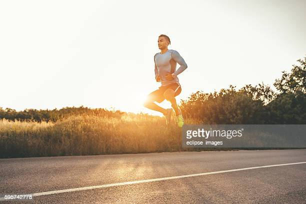 athletic man exercising jumps outdoors - high up stock photos and pictures