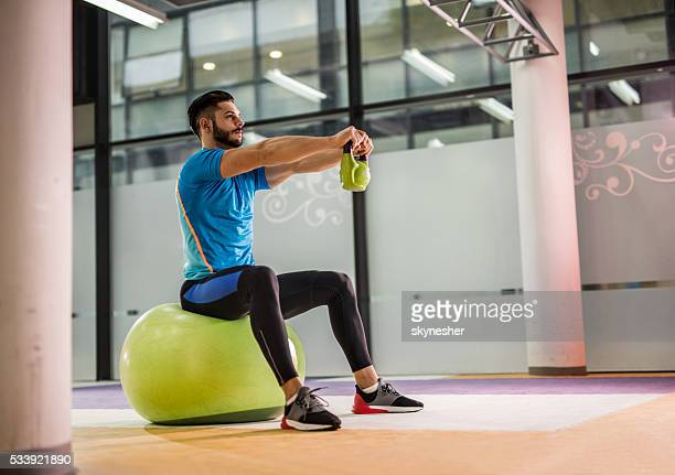 athletic man exercising with kettle bell in a gym. - fitness ball stock pictures, royalty-free photos & images