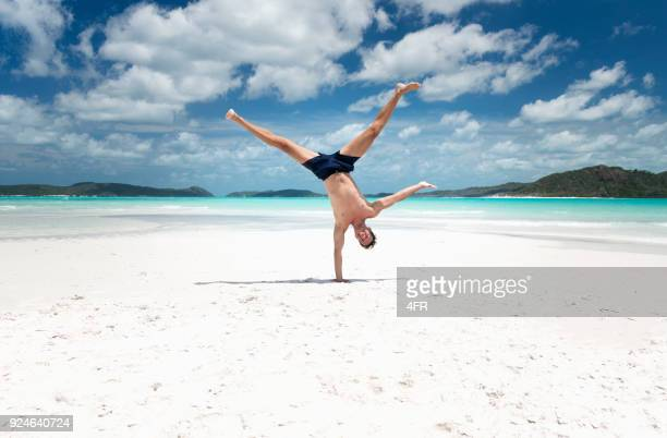athletic man in a capoeira pose, whitsunday islands, queensland, australia - handstand stock pictures, royalty-free photos & images