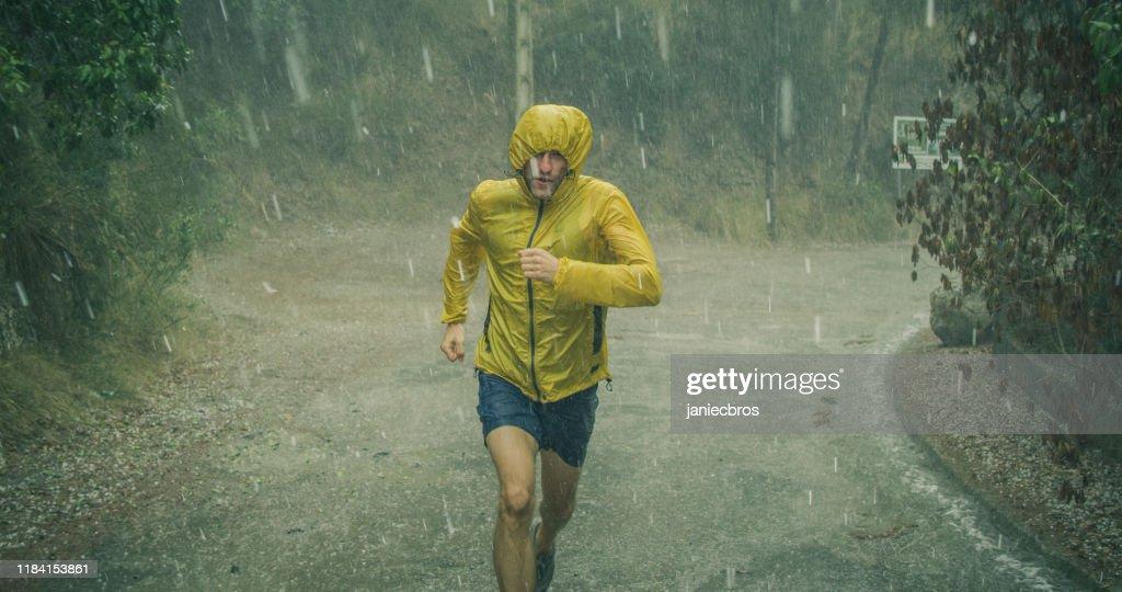 Uomo atletico che fa jogging in condizioni meteorologiche estreme. Grandine e pioggia : Foto stock