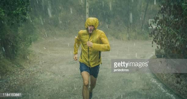 uomo atletico che fa jogging in condizioni meteorologiche estreme. grandine e pioggia - rovescio foto e immagini stock