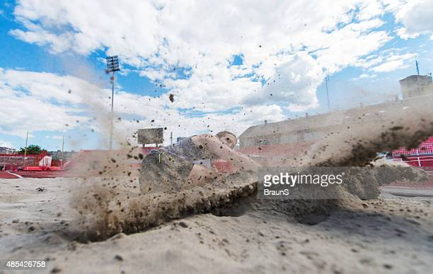 athletic man landing in a sand after a long jump. - long jump stock pictures, royalty-free photos & images