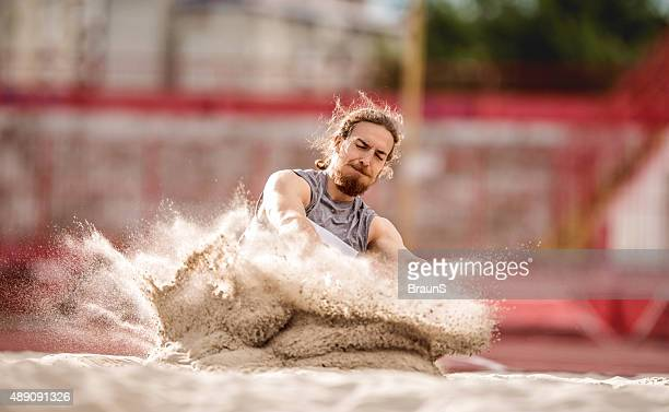 Athletic man landing in a sand after a long jump.