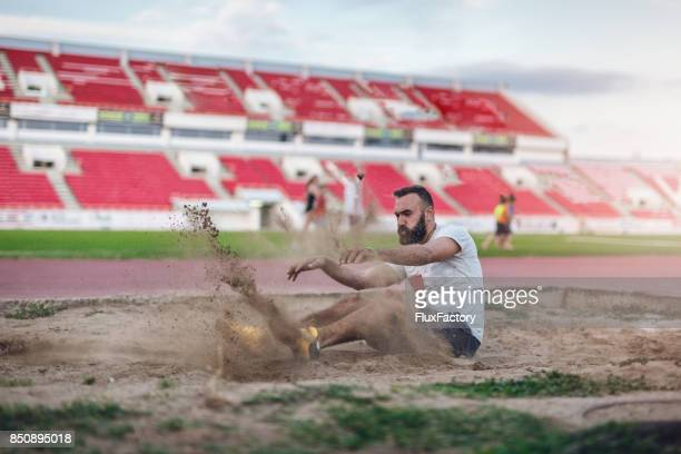 Athletic man landing in a sand