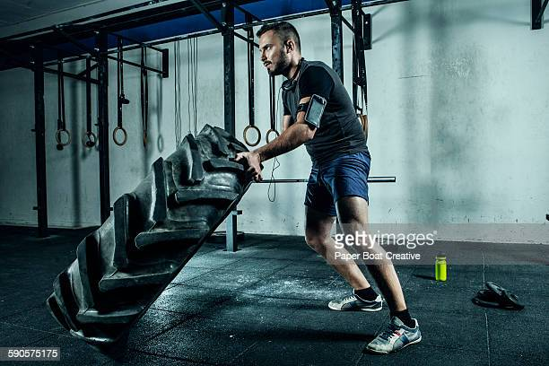 Athletic man lifting a large gym tire in gym