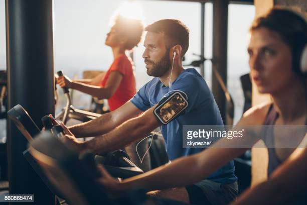Athletic man listening music while exercising on spinning class in a gym.