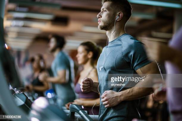athletic man listening music while running on treadmill in a gym. - health club stock pictures, royalty-free photos & images