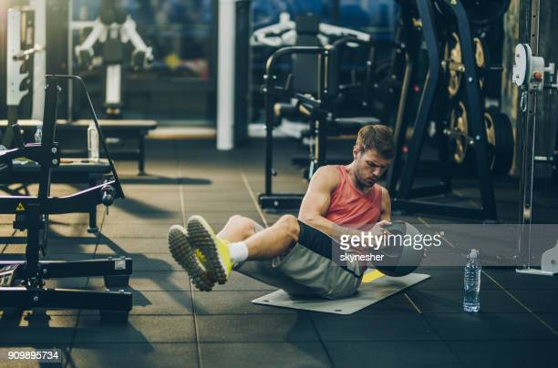 athletic man making an effort while exercising sit-ups with medicine ball in a gym. - medicine ball stock pictures, royalty-free photos & images
