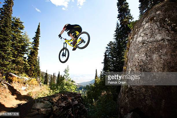 A athletic man mountain biking jumps off a large cliff while downhilling in Wyoming.