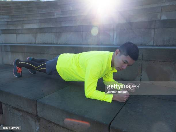 athletic man performing a plank exercise. - one mid adult man only stock pictures, royalty-free photos & images