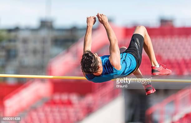 Homme athlétique performant saut en hauteur sur une concurrence.