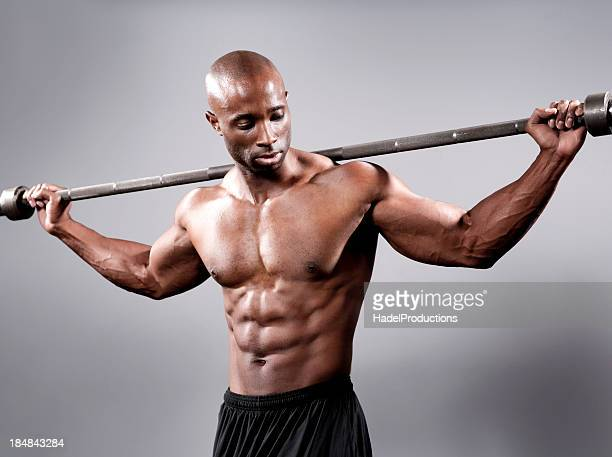 athletic man posing with a barbell - black male bodybuilders stock photos and pictures