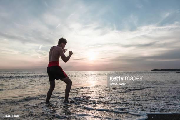 athletic man practicing martial arts on the beach at sunset - ランニングショートパンツ ストックフォトと画像