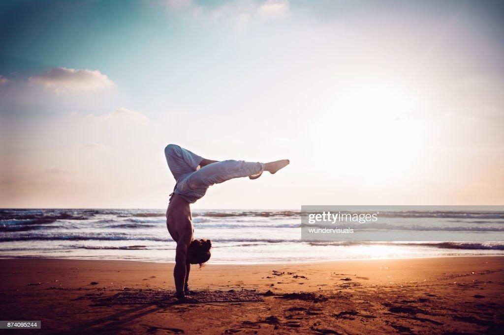 Atlético homem praticando ioga na praia ao pôr do sol : Foto de stock