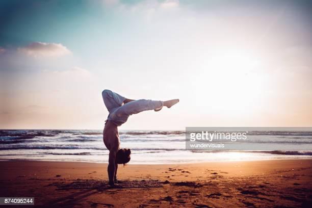 Sportlicher Mann üben Yoga am Strand bei Sonnenuntergang