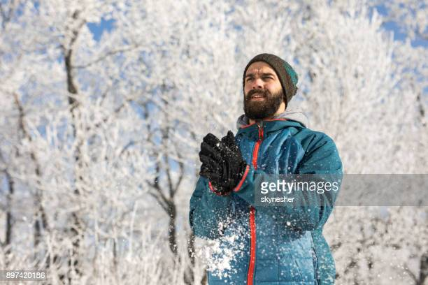 Athletic man preparing for sports training during cold winter day in nature.