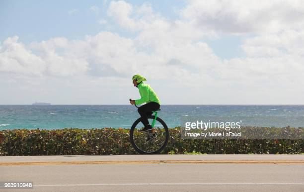 Athletic man riding a unicycle along the coastline