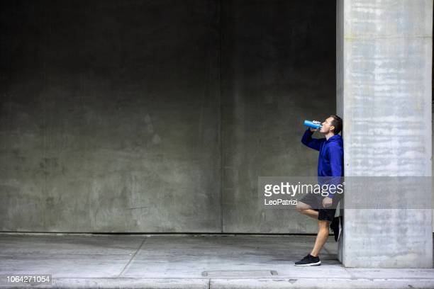 athletic man running and getting fit in the city downtown after work - energy drink stock pictures, royalty-free photos & images