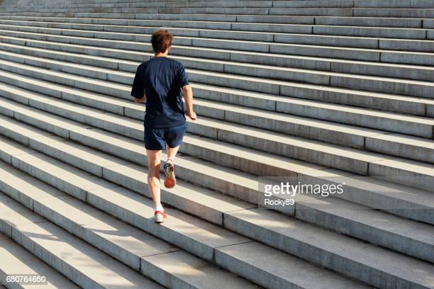 Athletic man running endless stairs