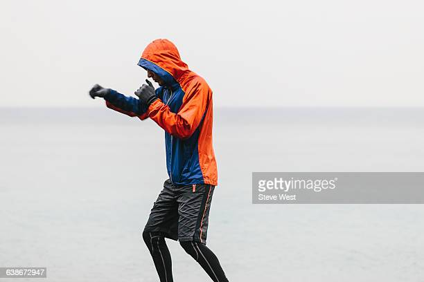 Athletic man shadowboxing in the rain