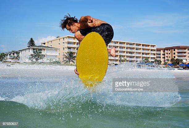 athletic man skimboarding doing a full turn catches air - st. petersburg florida stock photos and pictures