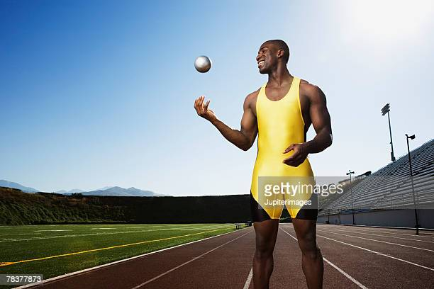 athletic man tossing up shot put - shot put stock pictures, royalty-free photos & images