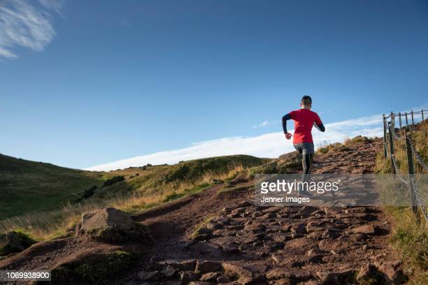 athletic man trail running up a mountainside. - extreme terrain stock pictures, royalty-free photos & images