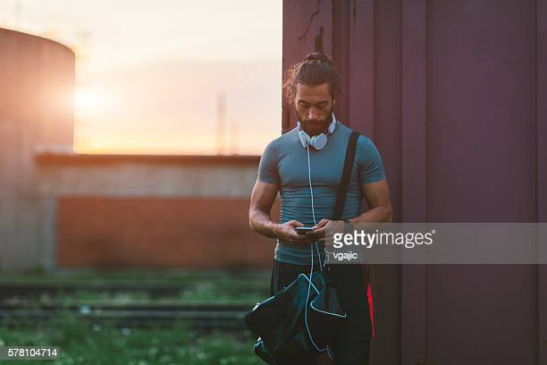 Athletic Man Using His Smart Phone After Running.