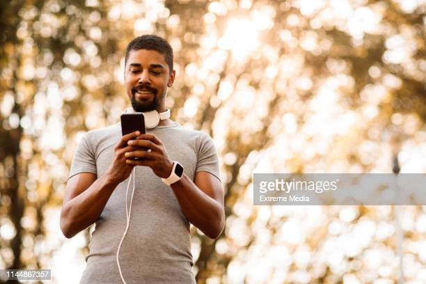 athletic man with headphones around his neck typing a message on a smart phone - phone message stock pictures, royalty-free photos & images