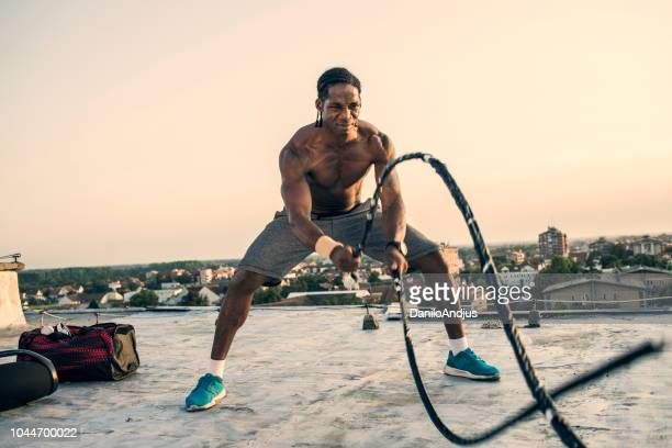 athletic man working out on the roof - cross training stock pictures, royalty-free photos & images