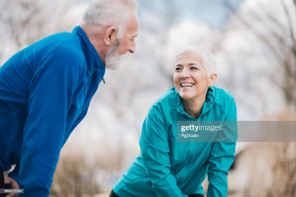 Athletic mature couple smiling and exercising together : Stock Photo
