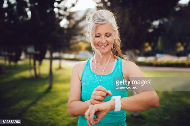 Athletic mature woman monitoring her running performance on smartwatch