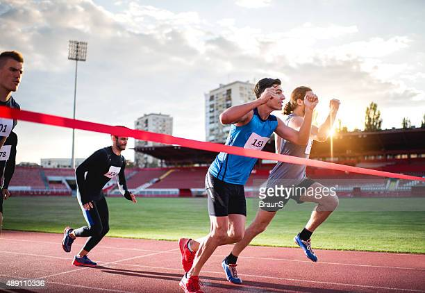 athletic men about to cross the finish line . - finishing line stock pictures, royalty-free photos & images