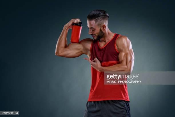 Athletic Men holding Nutritional Supplement Bottle