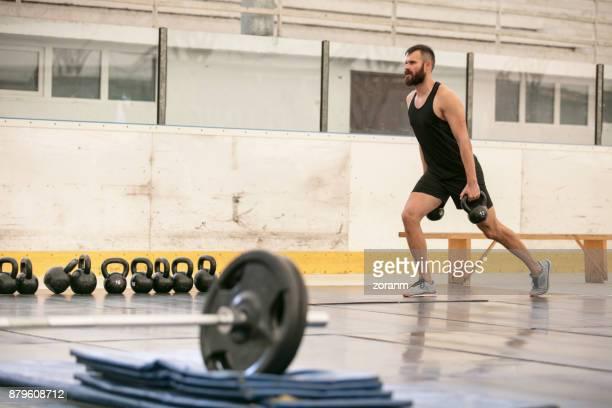 Athletic men using kettlebells in cross training