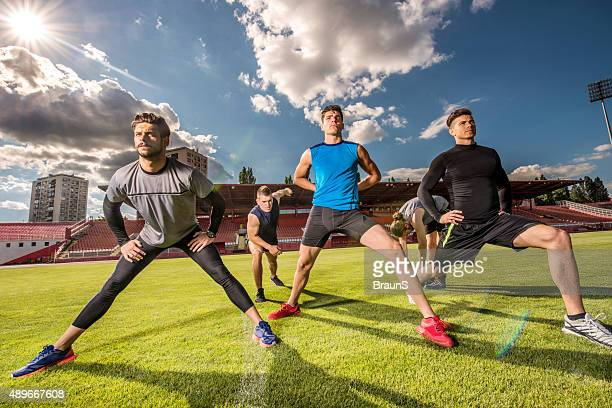Athletic men warming up before sports training on a stadium.