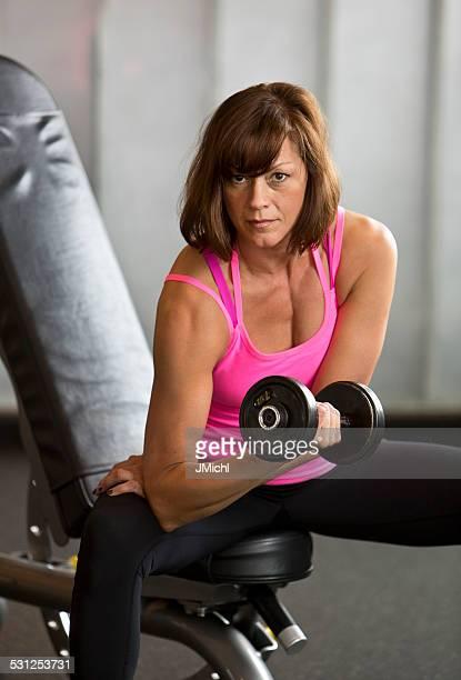 Athletic de mediana edad mujer haciendo ejercicio de levantamiento de pesas.
