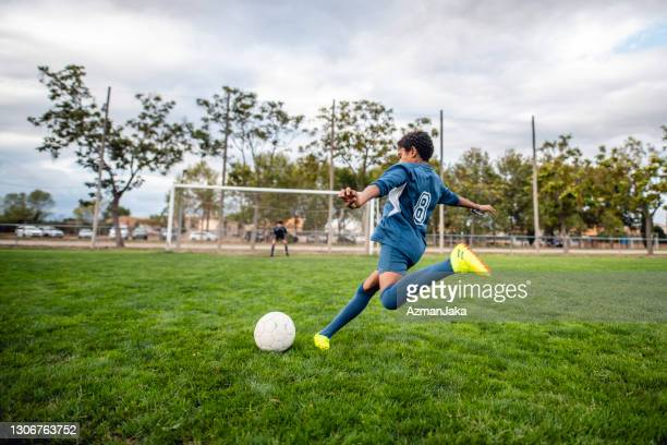 athletic mixed race boy footballer approaching ball for kick - soccer competition stock pictures, royalty-free photos & images